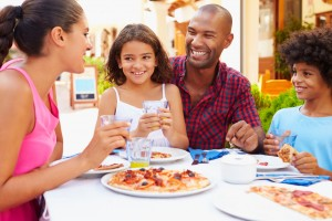 Family Eating Meal At Outdoor Restaurant Together